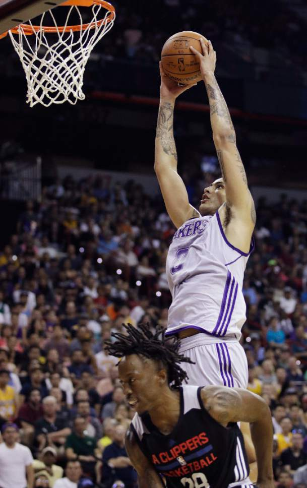 Los Angeles Lakers' Kyle Kuzma dunks over Los Angeles Clippers' Jaron Johnson during the second half of an NBA summer league basketball game, Friday, July 7, 2017, in Las Vegas. (AP Photo/John Locher)