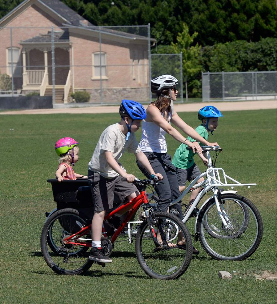 Al Hartmann  |  The Salt Lake Tribune   Heather May, her sons, Jack, 10, and Luke, 8, ride their bikes to the Holladay Park Thursday, June 22, 2017, before it gets too hot. Her daughter Margot rides in the big bucket on her bike.