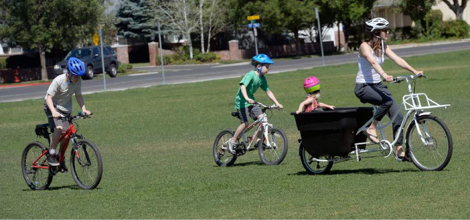 Al Hartmann  |  The Salt Lake Tribune Heather May, her sons, Jack, 10, and Luke, 8, ride their bikes to the Holladay Park Thursday, June 22, 2017, before it gets too hot.  Her daughter Margot, almost three years old, rides in the big bucket on her bike.