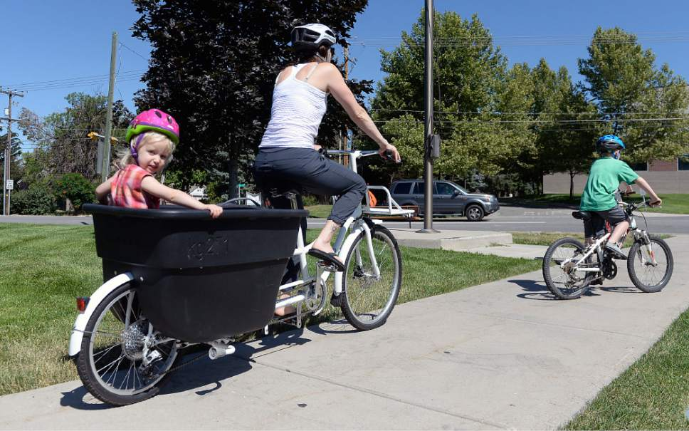 Al Hartmann  |  The Salt Lake Tribune   Heather May saddles up her sons, Jack, 10, and Luke, 8, on their bikes at the Holladay Library Thursday, June 22, 2017.  Her daughter Margot, almost three years old, rides in the big bucket on her bike as they go to the park before it gets too hot.