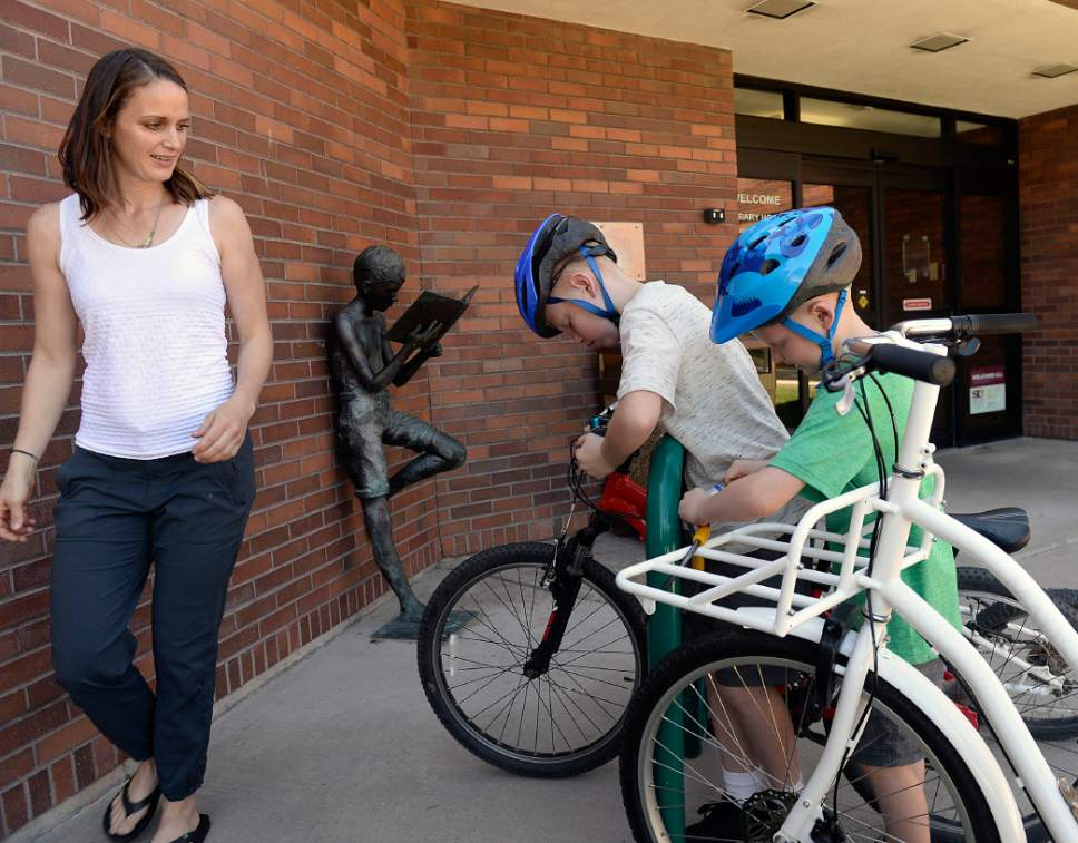Al Hartmann  |  The Salt Lake Tribune   Heather May saddles up her sons, Jack, 10, and Luke, 8, on their bikes at the Holladay Library, Thursday, June 22, 2017.  Her daughter Margot, almost three years old, rides in the big bucket on her bike as they go to park before it gets too hot.