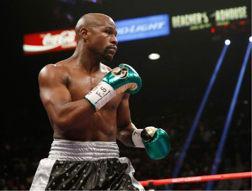 FILE - In this Sept. 12, 2015, file photo, Floyd Mayweather Jr. fights Andre Berto (not shown) during their welterweight title in Las Vegas. It's still early, but give Round 1 of the trash talk battle between Conor McGregor and Mayweather Jr. to the Irish MMA star. (AP Photo/Steve Marcus, File)