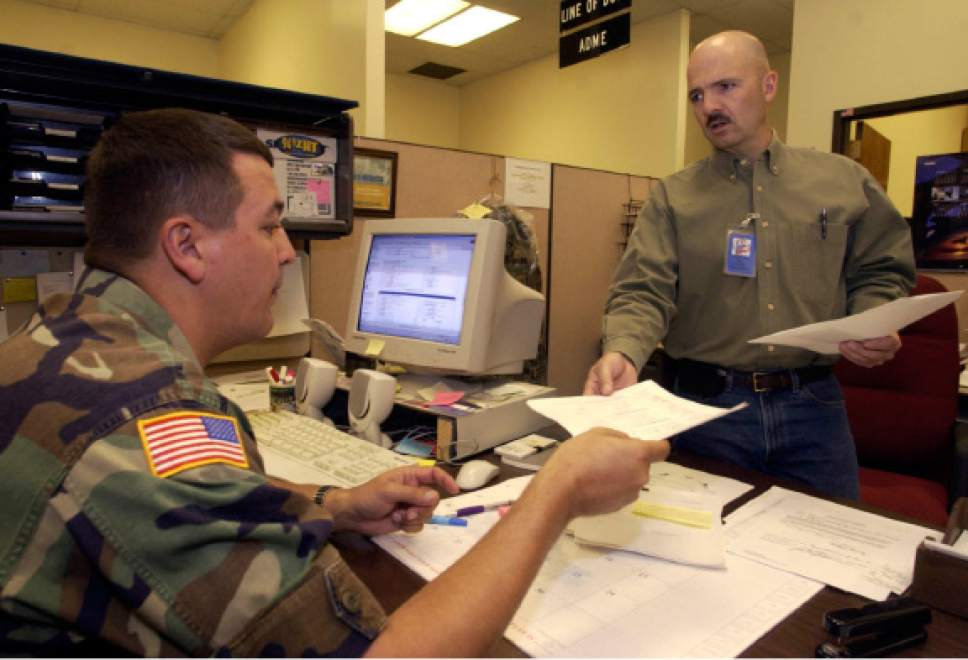 |  Tribune File Photo  SFC Layne Morris (right) receives his papers to return to Ft. Carson from SSG. Roland Knox at the Army national Guard Headquarters in Draper Monday April 19, 2004.