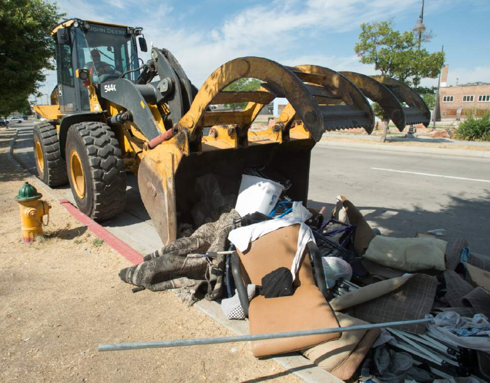Rick Egan  |  The Salt Lake Tribune  Heavy machinery picks up trash left by homeless campers in the Rio Grande area of Salt Lake City, during the Salt Lake County Health Department's cleanup on Thursday, July 6, 2017. The biggest challenge for crews is the disposal of syringes discarded by drug users.