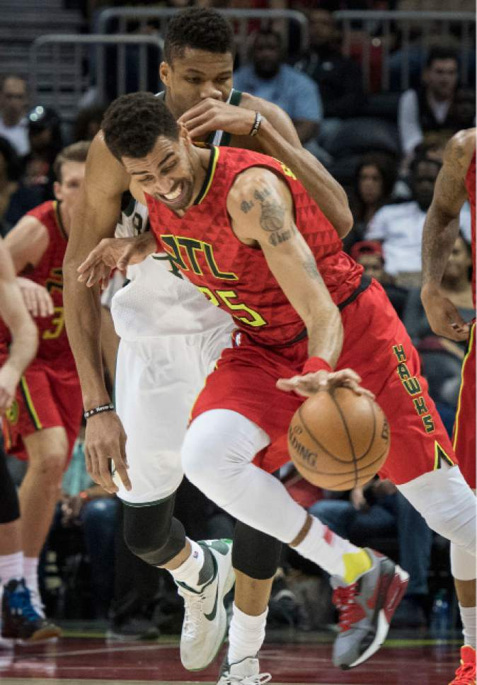 Atlanta Hawks forward Thabo Sefolosha, front, of Switzerland, steals the ball in front of Milwaukee Bucks forward Giannis Antetokounmpo, of Greece, during the second half of an NBA basketball game, Sunday, Jan. 15, 2017, in Atlanta. (AP Photo/John Amis)