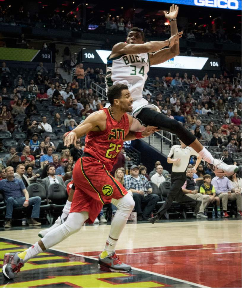 Milwaukee Bucks forward Giannis Antetokounmpo (34), of Greece, comes down after attempting to block the shot of Atlanta Hawks forward Thabo Sefolosha, of Switzerland, during the first half of an NBA basketball game, Sunday, Jan. 15, 2017, in Atlanta. (AP Photo/John Amis)