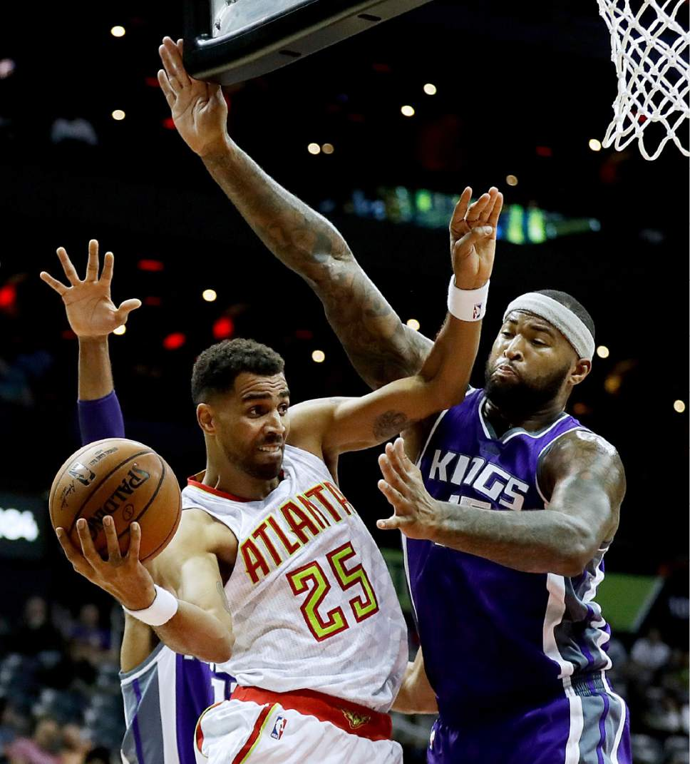 Atlanta Hawks' Thabo Sefolosha (25) of Switzerland, puts up a shot against the defense of Sacramento Kings' Garrett Temple, rear, and DeMarcus Cousins, right, in the second quarter of an NBA basketball game in Atlanta, Monday, Oct. 31, 2016. (AP Photo/David Goldman)