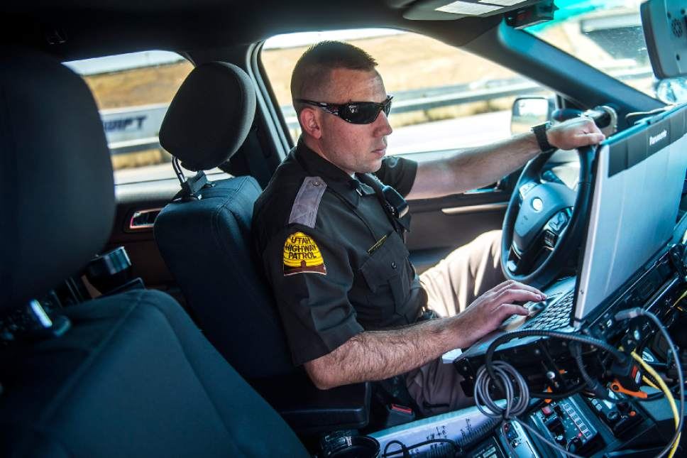 Chris Detrick  |  The Salt Lake Tribune Utah Highway Patrol Trooper Derek Shelby writes a citation for a driver who was pulled over for distracted driving on Interstate 15 Thursday, July 13, 2017.