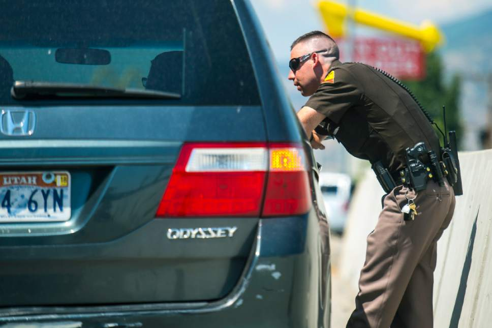 Chris Detrick  |  The Salt Lake Tribune Utah Highway Patrol Trooper Derek Shelby talks to a driver who was pulled over for distracted driving on Interstate 15 Thursday, July 13, 2017.