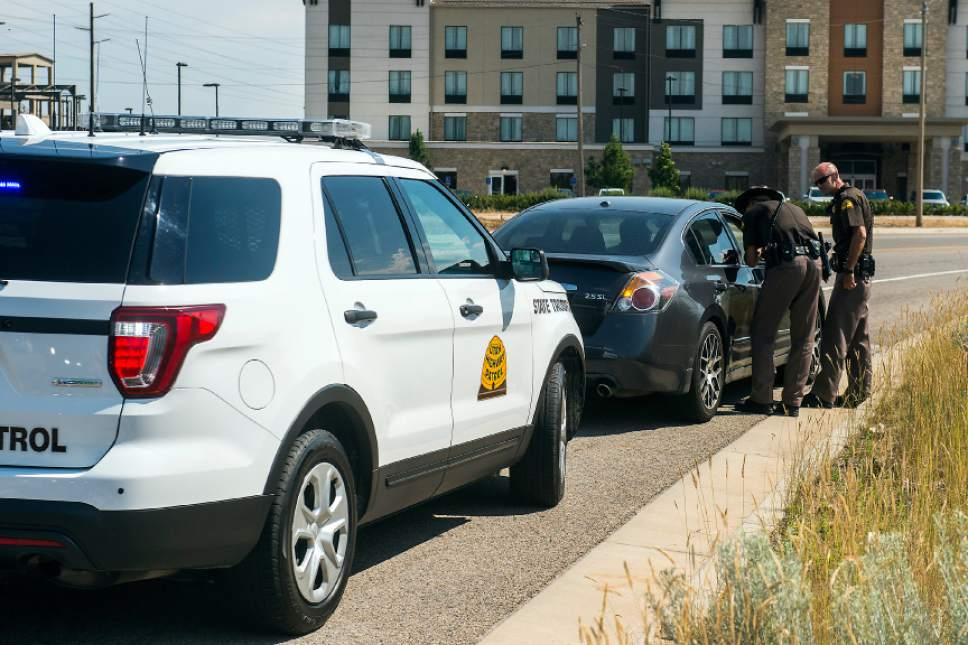 Chris Detrick  |  The Salt Lake Tribune Utah Highway Patrol Lieutenant Beau Mason, left, and Corporal Mark Thompson talk to a driver who was pulled over for using his cellphone on Interstate 15 Thursday, July 13, 2017.