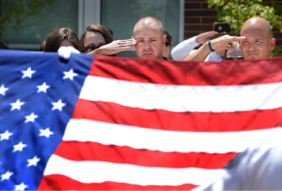 """Scott Sommerdorf      The Salt Lake Tribune   Sgt. Chad Reyes salutes as the flag draping his K-9 partner's casket is lifted to be folded at the memorial service for """"Dingo,"""" a Unified Police Department dog shot and killed in the line of duty July 6 while working with his K-9 handler Sgt. Chad Reyes, Saturday, July 15, 2017."""