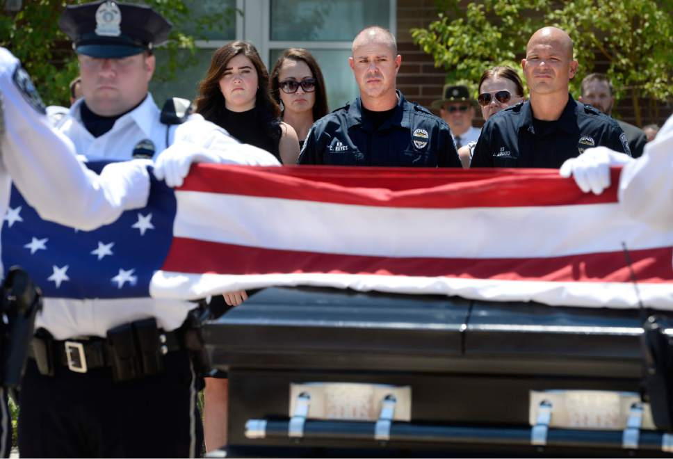 """Scott Sommerdorf      The Salt Lake Tribune   Sgt. Chad Reyes watches as the flag draping his K-9 partner's casket is lifted to be folded at the memorial service for """"Dingo,"""" a Unified Police Department dog shot and killed in the line of duty July 6 while working with his K-9 handler Sgt. Chad Reyes, Saturday, July 15, 2017."""