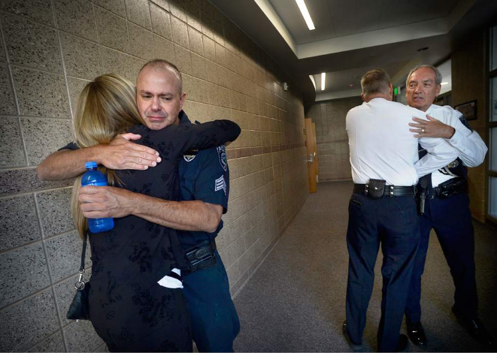 """Scott Sommerdorf      The Salt Lake Tribune   Sgt. Chad Reyes, left, gets a hug from Shawn Winder, Sheriff Jim Winder's wife prior to the memorial service for """"Dingo,"""" a Unified Police Department dog shot and killed in the line of duty July 6 while working with his K-9 handler Sgt. Chad Reyes, Saturday, July 15, 2017."""