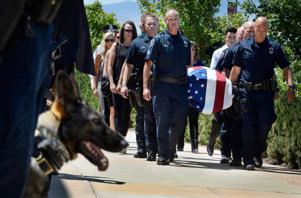 """Scott Sommerdorf      The Salt Lake Tribune   Sgt. Chad Reyes, center, and pall bearers take """"Dingo,"""" past a cordon of police dogs after a memorial service for the Unified Police Department dog shot and killed in the line of duty July 6 while working to apprehend a suspect. Sgt. Reyes was Dingo's handler, and was promoted to Lieutenant by Sheriff Jim Winder during the ceremony, Saturday, July 15, 2017."""