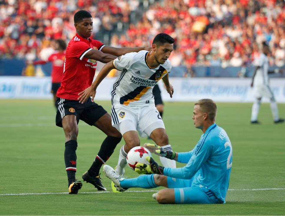 Los Angeles Galaxy goalkeeper Jon Kempin, bottom, grabs the ball in front of Manchester United's Marcus Rashford, left, and Galaxy's Hugo Arellano during the first half of a friendly soccer match Saturday, July 15, 2017, in Carson, Calif. (AP Photo/Jae C. Hong)