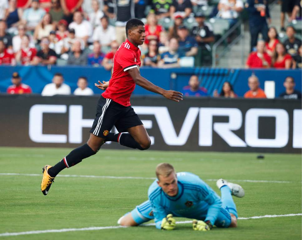 Manchester United's Marcus Rashford, top, runs past Los Angeles Galaxy goalkeeper Jon Kempin after scoring a goal during the first half of a friendly soccer match Saturday, July 15, 2017, in Carson, Calif. (AP Photo/Jae C. Hong)