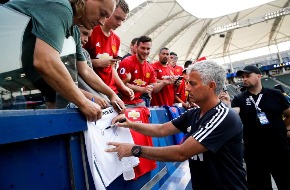 Manchester United head coach Jose Mourinho gives autographs before the team's friendly soccer match against the Los Angeles Galaxy, Saturday, July 15, 2017, in Carson, Calif. (AP Photo/Jae C. Hong)