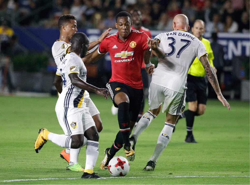 Manchester United's Anthony Martial, center, is pressured by Los Angeles Galaxy's Jelle Van Damme, right, Ema Boateng, front, and Giovani dos Santos during the second half of a friendly soccer match Saturday, July 15, 2017, in Carson, Calif. Manchester United won 5-2. (AP Photo/Jae C. Hong)