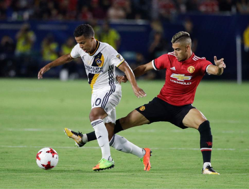 Los Angeles Galaxy's Giovani dos Santos, left, is pressured by Manchester United's Andreas Pereira during the second half of a friendly soccer match Saturday, July 15, 2017, in Carson, Calif. Manchester United won 5-2. (AP Photo/Jae C. Hong)