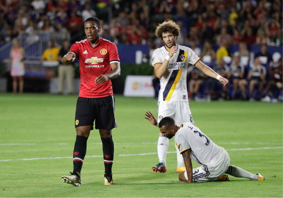 Manchester United's Anthony Martial, left, points to a teammate as he walks past Los Angeles Galaxy's Ashley Cole, bottom, and Joao Pedro after scoring a goal during the second half of a friendly soccer match Saturday, July 15, 2017, in Carson, Calif. Manchester United won 5-2. (AP Photo/Jae C. Hong)