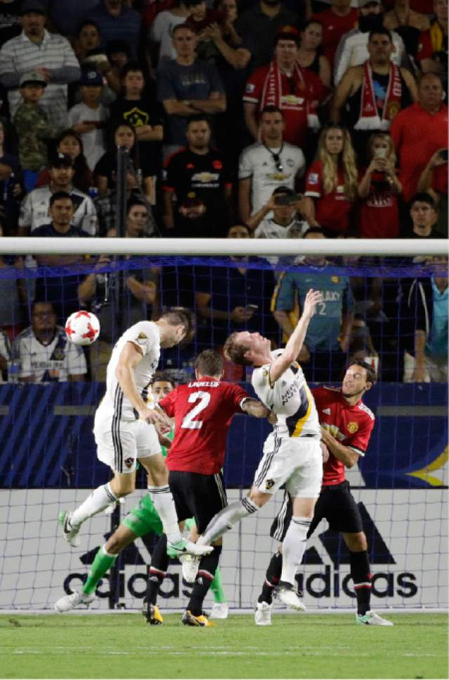 Fans watch as Los Angeles Galaxy's Dave Romney, left, heads the ball for a goal during the second half of the team's friendly soccer match against Manchester United on Saturday, July 15, 2017, in Carson, Calif. Manchester United won 5-2. (AP Photo/Jae C. Hong)