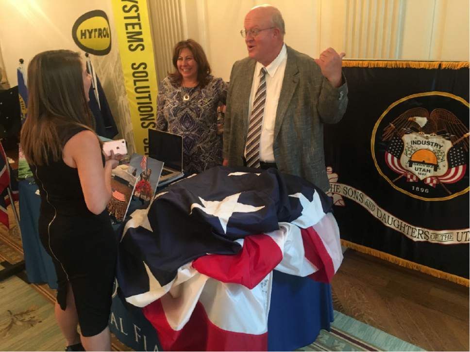 Thomas Burr  |  The Salt Lake Tribune   Paul Swenson, president of Utah-based Colonial Flag, motions to the Utah state flag while talking to a visitor at the White House on Monday as part of the Trump administration's showcase of Made in America products. On the left is Valerie Kelly, also of Colonial Flag.