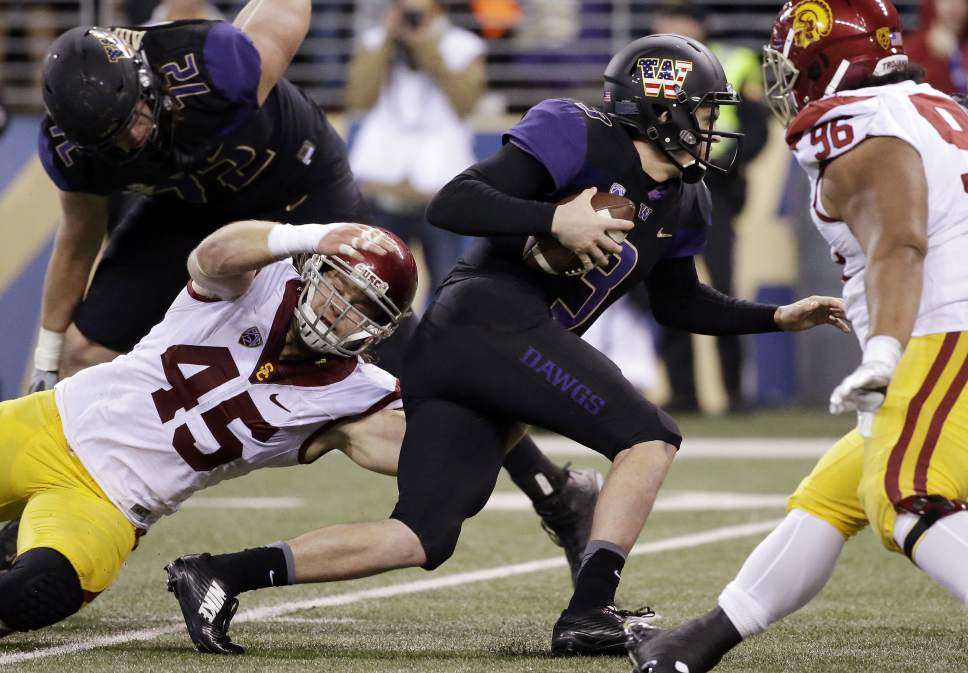 Southern California defensive end Porter Gustin (45) grabs Washington quarterback Jake Browning for a sack in the second half of an NCAA college football game Saturday, Nov. 12, 2016, in Seattle. USC won 26-13. (AP Photo/Elaine Thompson)