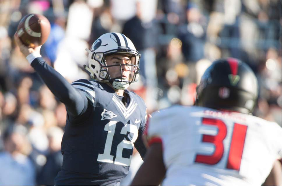 Rick Egan     The Salt Lake Tribune  Brigham Young Cougars quarterback Tanner Mangum (12) throws down field,  as Fresno State Bulldogs linebacker Ejiro Ederaine (31) defends in football action, as BYU defeated the Fresno Bulldogs 52 -10, at Lavell Edwards stadium, Tuesday, November 21, 2015.