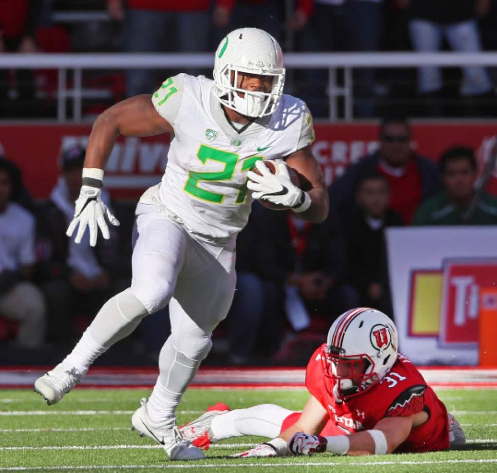 Oregon running back Royce Freeman (21), runs out of the tackle of Utah linebacker Evan Eggiman (31) in the second half during an NCAA college football game, Saturday, Nov. 19, 2016, in Salt Lake City. Oregon defeated Utah 30-28. (AP Photo/George Frey)