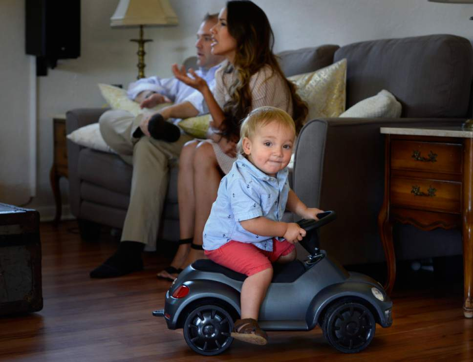 Scott Sommerdorf | The Salt Lake Tribune Benjamin Sessions with his wife, Heather, talks with a visitor as their fifteen- month-old son, Gaius, plays nearby in their Sugar House home, Wednesday, June 14, 2017.