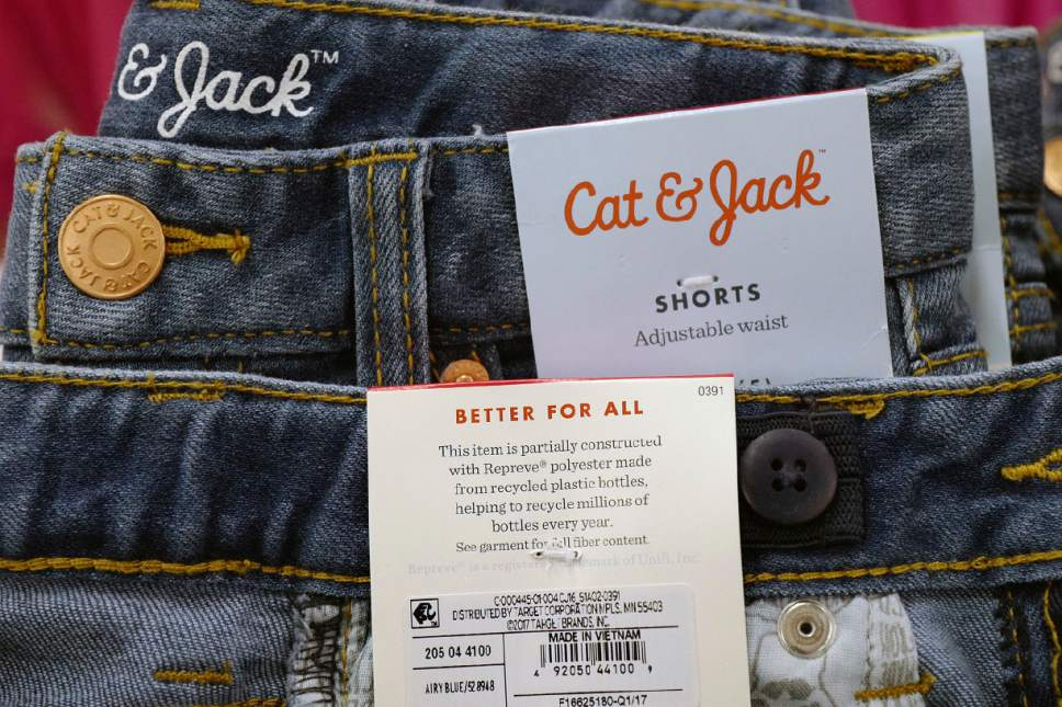 In this Friday, July 14, 2017, photo, Cat & Jack jeans are on display at a Target store, in New York. The jeans are made with Repreve polyester fabric, created from recycled plastic bottles. For this year's back-to-school shopping season, green is the new black. Increasingly, parents and their kids are looking for second-hand clothing or fashions made from reused material. (AP Photo/Mark Lennihan)