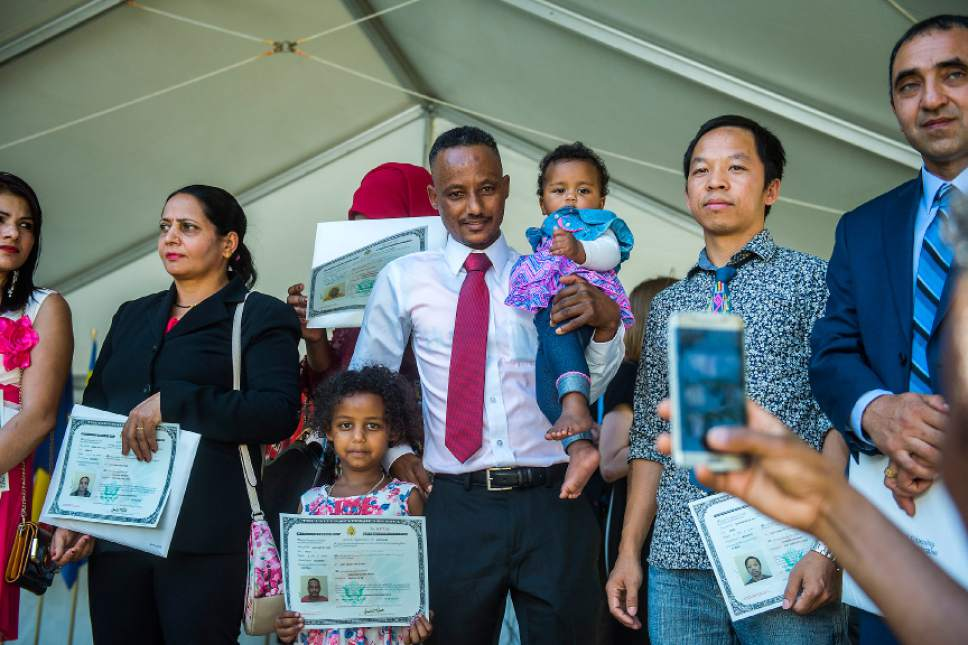 Chris Detrick  |  The Salt Lake Tribune  Abraham Hagos, 31, from Eritrea, poses for a picture with his daughters Kynte, 9 months, and Washington, 6, after becoming a citizen of United States of America during World Refugee Day at Liberty Park on Saturday, July 15, 2017.
