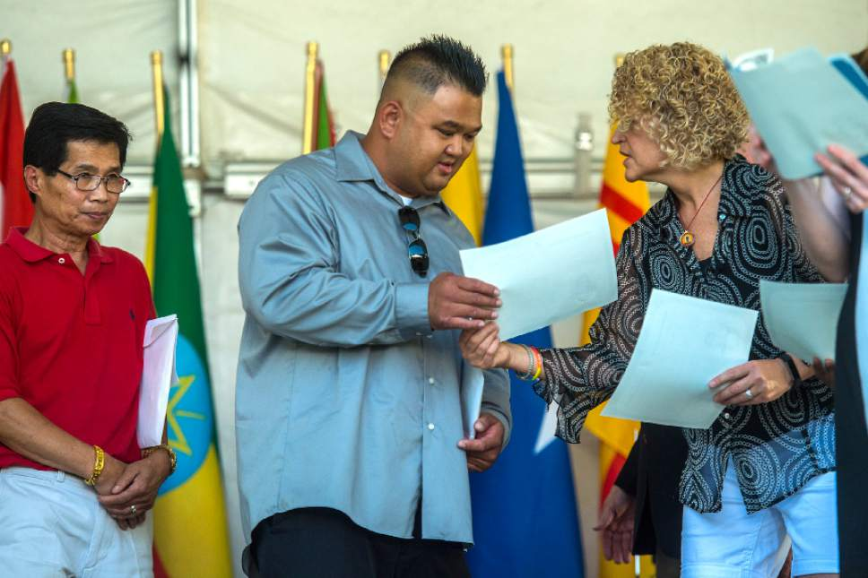 Chris Detrick  |  The Salt Lake Tribune Vilakone Lithamalay, 37, of West Valley City, receives a certificate from Salt Lake City Mayor Jackie Biskupski  during World Refugee Day at Liberty Park Saturday, July 15, 2017. Lithamalay became a citizen of United States of America after having lived here for the past 29 years.