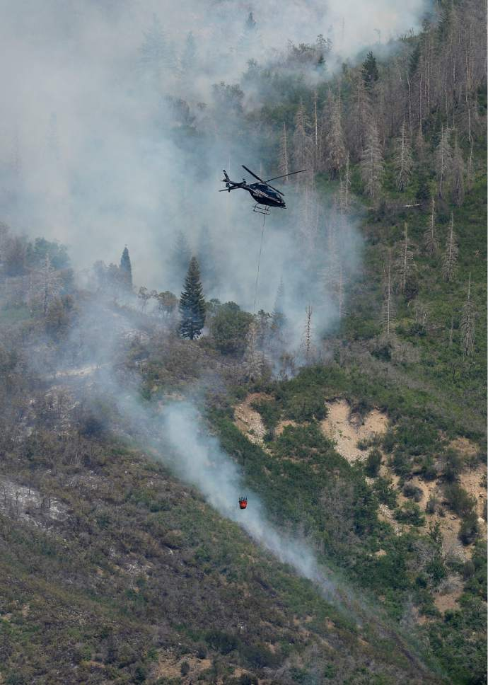 Scott Sommerdorf   |  The Salt Lake Tribune   A fire fighting helicopter works to put out hot spots in the hills above Alpine, Sunday, July 16, 2017.