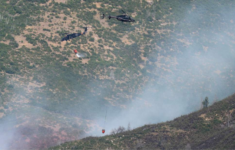 Scott Sommerdorf   |  The Salt Lake Tribune   Fire fighting helicopters criss cross as they put out hot spots in the hills above Alpine, Sunday, July 16, 2017.