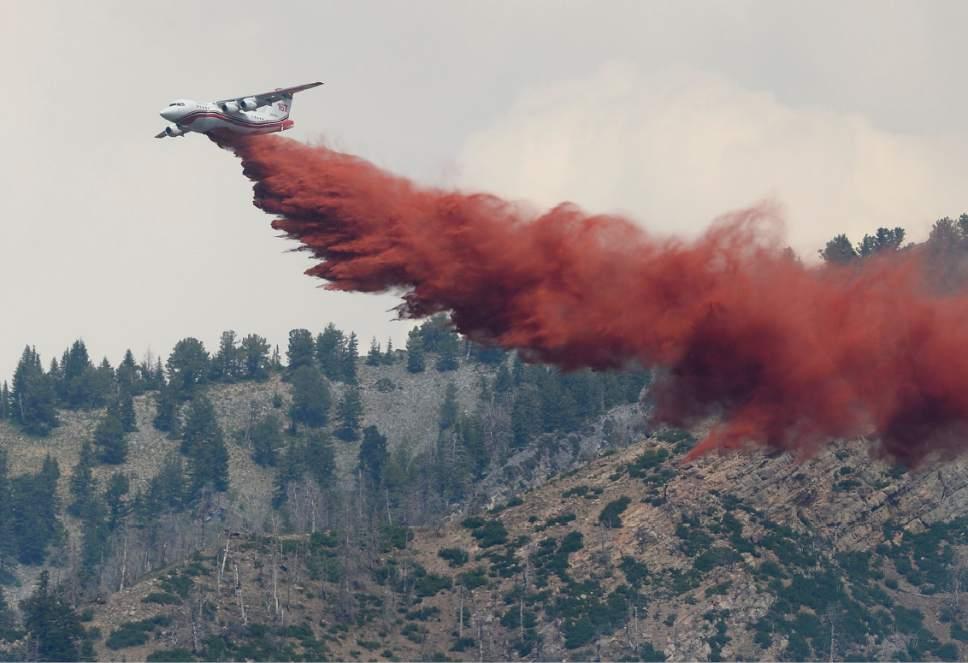 Scott Sommerdorf   |  The Salt Lake Tribune   An air tanker drops retardant onto hot spots in the hills above Alpine, Sunday, July 16, 2017.