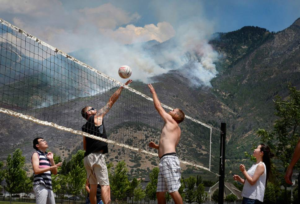 Scott Sommerdorf   |  The Salt Lake Tribune   The Victor family plays volleyball as aerial crews fight the fires being driven uphill as seen from Creekside Park in Alpine, Sunday, July 16, 2017.