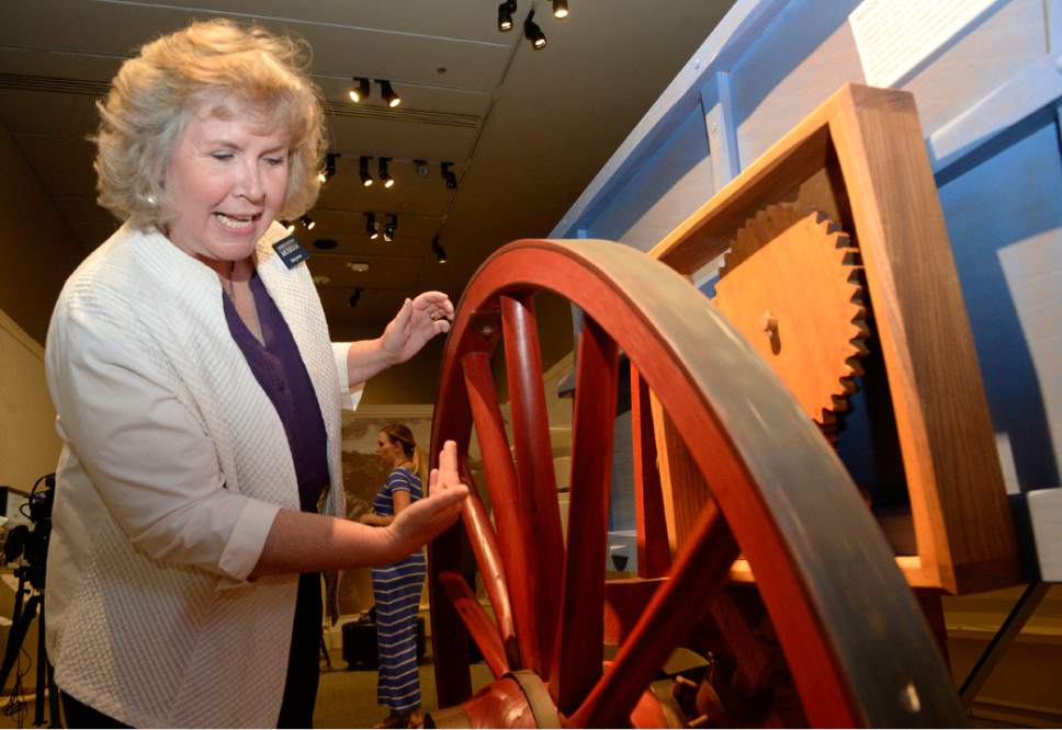 """Al Hartmann     The Salt Lake Tribune Maryanne Andrus, exhibit program manager at the Church History Museum, demonstrates the """"roadometer,"""" a device developed by Orson Pratt and William Clayton.  It was attached to a wagon's wheel and measured distance traveled by counting the number of times the wheel went around. It is one of the exhibits in """"Mormon Trails: Pathways to Zion,"""" a new exhibit at the LDS Church History Museum.  The exhibit opens Thursday, July 13."""