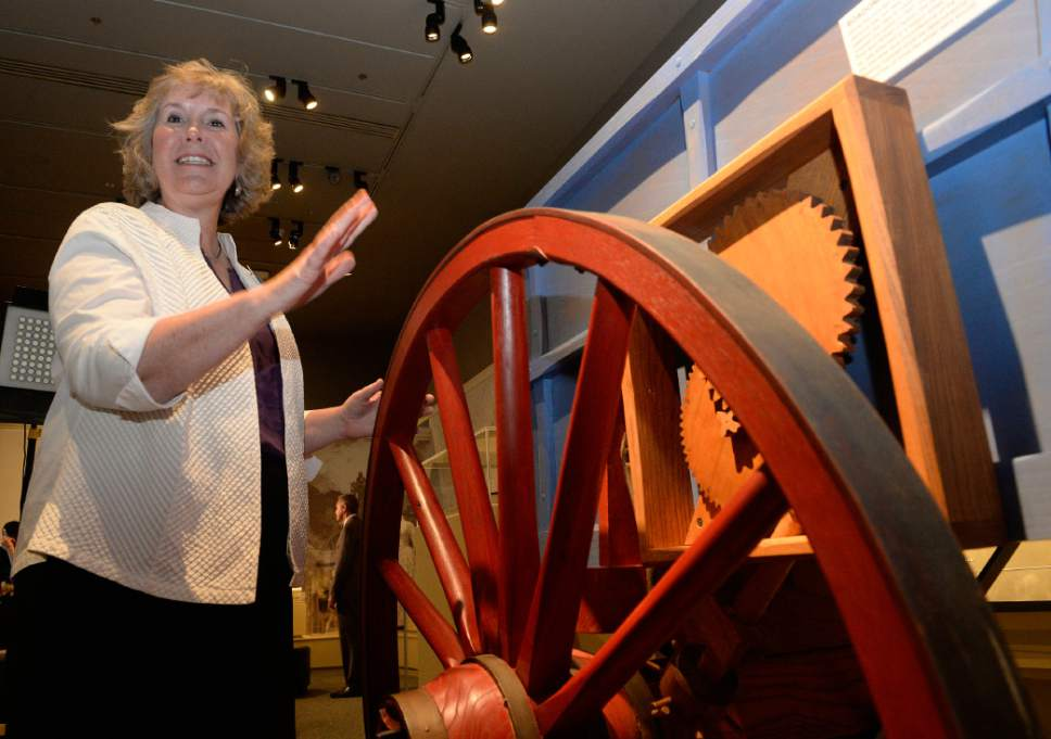 """Al Hartmann     The Salt Lake Tribune Maryanne Andrus, exhibit program manager at the Church History Museum, demonstrates the """"roadometer,""""  a device developed by Orson Pratt and William Clayton.  It was attached to a wagon's wheel and measured distance traveled by counting the number of times the wheel went around. It is one of the exhibits in """"Mormon Trails: Pathways to Zion,"""" a new exhibit at the LDS Church History Museum.  It opens Thursday, July 13."""