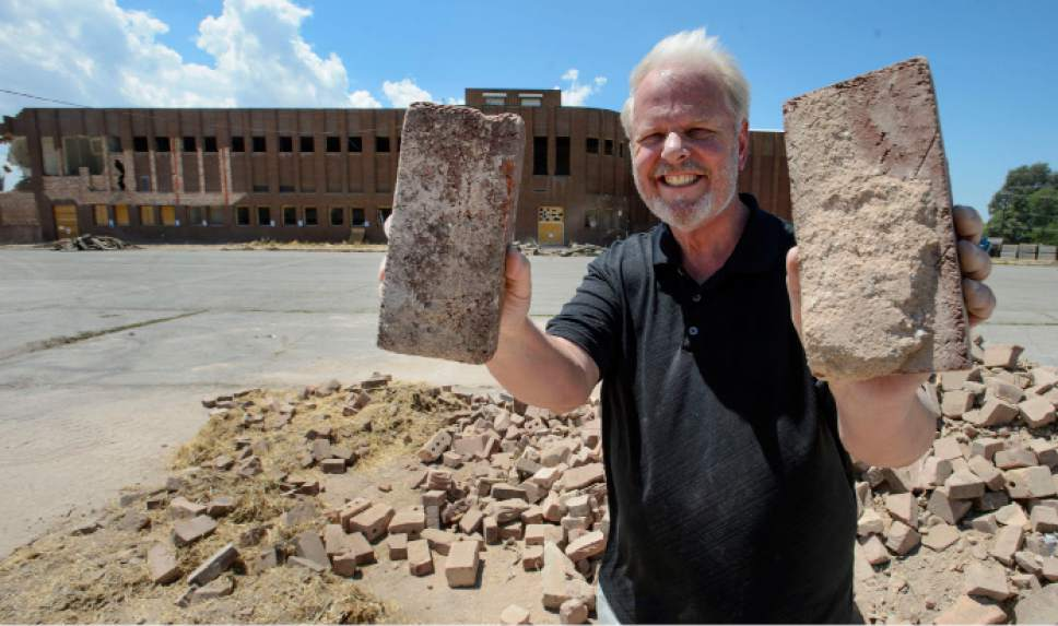 Steve Griffin  |  The Salt Lake Tribune   Frederick Dissel holds up bricks he picked up for his wife, Karen Gasparac Dissel who graduated from Granite in 1971, as Granite High School, behind, is demolished. Bricks from the school are being made available in the east parking lot in Salt Lake City Tuesday July 18, 2017.