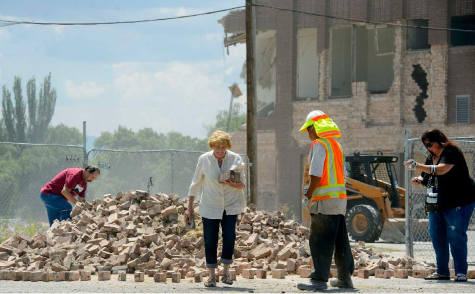 Steve Griffin  |  The Salt Lake Tribune   Valeen Zumbrunnen carries a few bricks she gathered from a pile as Grantie High School, behind, is demolished in Salt Lake City Tuesday July 18, 2017. Zumbrunnen worked at the school for ten years. Bricks from the school are being made available to the public in the east parking lot.