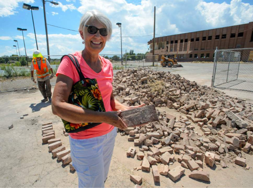 Steve Griffin  |  The Salt Lake Tribune   Deanna Nielsen with a brick she picked from a pile as Granite High School, behind, is demolished in Salt Lake City Tuesday July 18, 2017. Nielsen's 100-year-old mother, Ruth Lehman Johnson, graduated from Granite High in 1935. Bricks from the school are being made available to the public in the east parking lot.