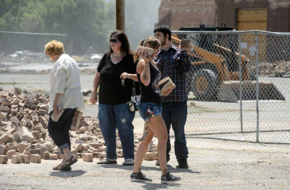 Steve Griffin  |  The Salt Lake Tribune   Granite High School graduate Misty Langford carries a few bricks from a pile as the old high school, behind, is demolished in Salt Lake City Tuesday July 18, 2017. Bricks from the school are being made available to the public in the east parking lot.