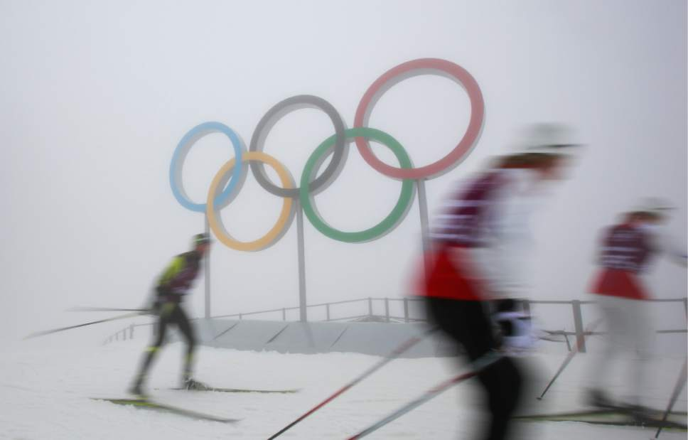 Cross-country skiers train in front of the olympic rings at the Laura biathlon and cross-country ski center, at the 2014 Winter Olympics, Monday, Feb. 17, 2014, in Krasnaya Polyana, Russia. After days of warm weather at the Sochi Olympics, fog up in the mountains is causing an even bigger disturbance. Thick fog rolled in over the mountains in Krasnaya Polyana on Sunday night and was still lingering on Monday, and the limited visibility forced organizers to delay a biathlon race and cancel the seeding runs in a snowboard event. (AP Photo/Gero Breloer)