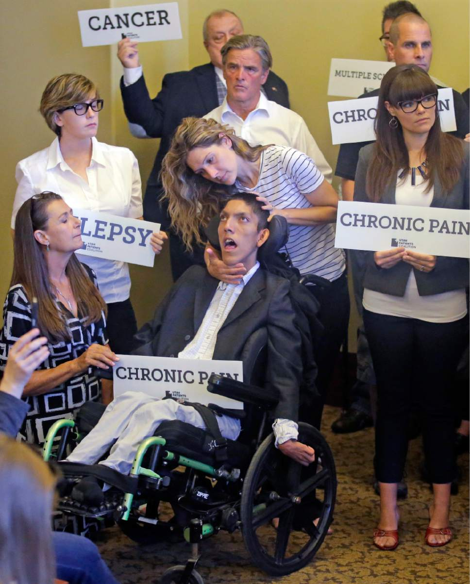 Rick Bowmer  |  The Associated Press Desiree Hennessy, center, attends to her adopted son Hestevan, who has cerebral palsy and suffers from chronic nerve pain, seizure disorder, during the Utah Patients Coalition news conference on June 26, 2017, in Salt Lake City. A group of activists and Utah residents with chronic conditions has launched a ballot initiative to ask voters next year to pass a broad medical marijuana law.