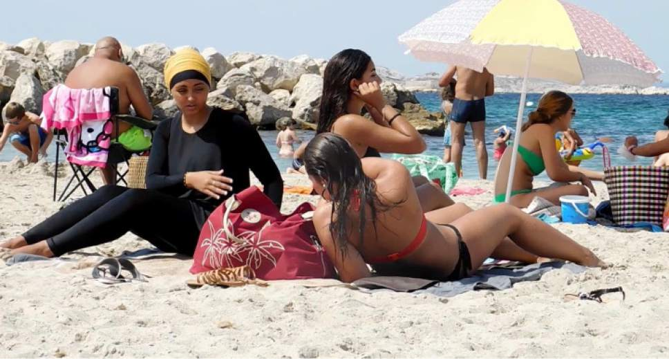 In this image taken from video, Nesrine Kenza who says she is happy to be free to wear a burkini, and two unidentified friends rest on the beach in Marseille, France, Monday Aug. 29, 2016.   A high court struck down the previous ban of the wearing of so called burkini Friday, but the debate revealed raw tensions between the secular establishment and sectors of France's estimated 5 million Muslims. (AP Photo)