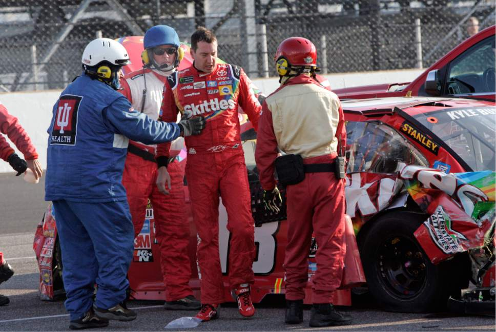 Kyle Busch, center, is lead away from his car after a crash with Martin