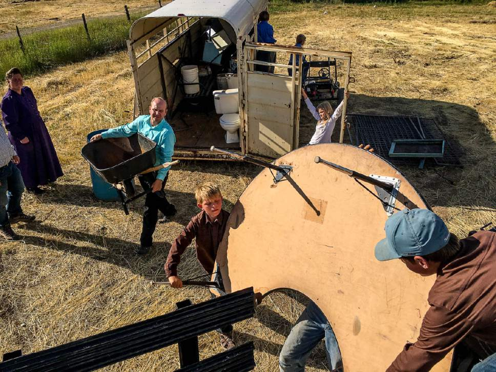 Trent Nelson  |  The Salt Lake Tribune Gabriel Owen, in green, helps load a truck and trailer for members of the FLDS polygamous sect living outside of Beaver, Saturday July 15, 2017. Owen and the Davis County Cooperative Society have been offering service and donations to needy FLDS members who were evicted from UEP homes in Hildale and Colorado City, Ariz.