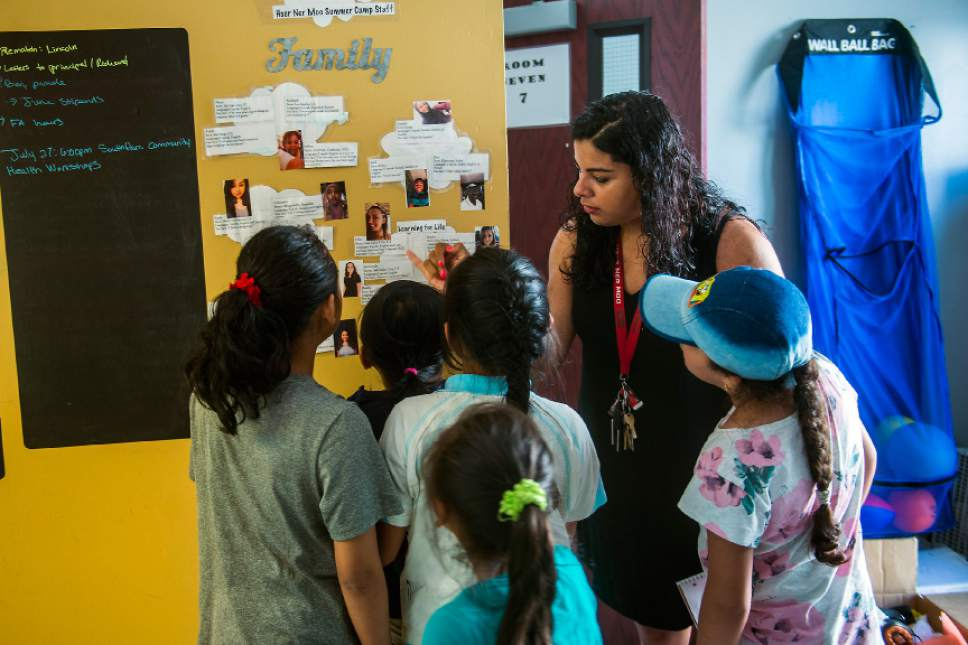 Chris Detrick  |  The Salt Lake Tribune Promise Site Coordinator Susie Estrada shows children pictures of the staff members at the Hser Ner Moo Community Center in South Salt Lake on Tuesday, July 18, 2017.