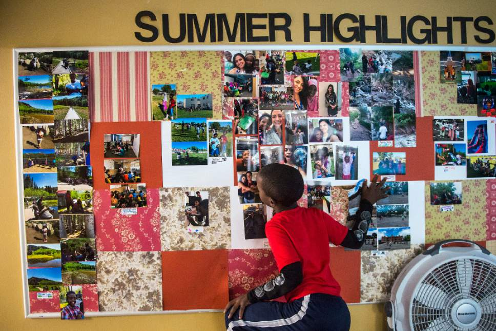 Chris Detrick  |  The Salt Lake Tribune  Abdi Mahad, 7, looks a photographs at the Hser Ner Moo Community Center in South Salt Lake on Tuesday, July 18, 2017.